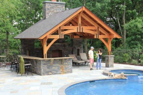 outdoor fireplace under pavilion by pool