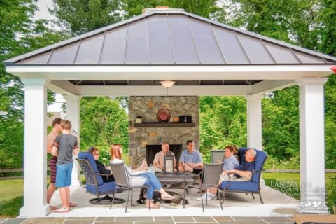 family hanging out outdoor fireplace under pavilion
