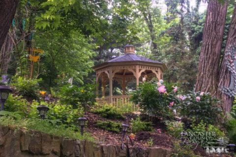 A Permanent Durable Gazebo In The Woods With Some Flowers Around It