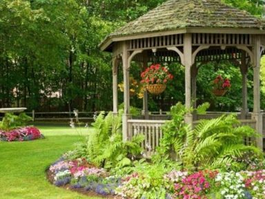 An Irresistible Wooden Gazebo In The Garden With Some Colorful Flowers Next To It